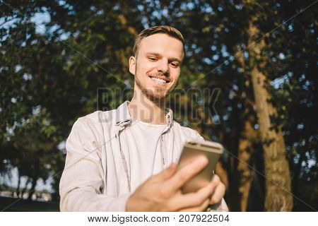 Awesome and good-looking young man is standing in a park and holding a phone in his hands. He is looking to the screen and smiling. Close up. Cut view