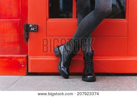 Red door and women's legs in black boots