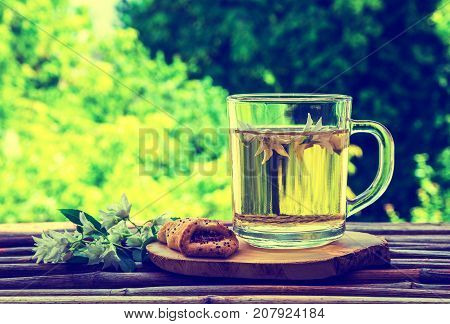 Glass cup of herbal tea jasmine tea and jasmine flowers on an old wooden table with a blurred green natural background. The concept of tea retro style