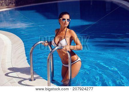 beautiful tanned young woman in bikini relaxing in swimming pool. outdoor shot on tenerife island. copyspace.