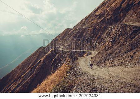 Spectacular and dangerous mountain road, Tusheti, Georgia. Adventure concept. Mount landscape. Unpaved winding road. Dirt serpentine road. Sunlight rays. Explore the world. Travel to Caucasus. Autumn
