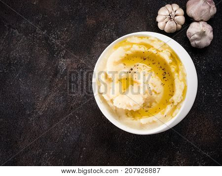 Mashed potatoes with spices and olive oil in white bowl on dark concrete background. Top view or flat lay. Copy space.