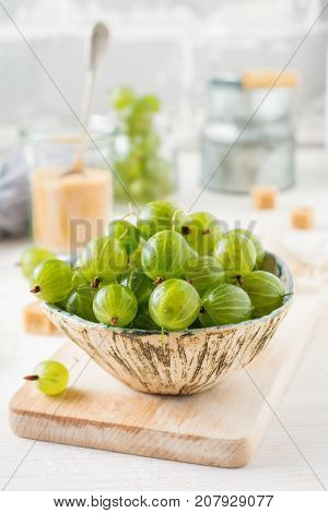 Fresh raw gooseberry berries in white ceramic plate on light wooden background. Selective focus. Rustic style.