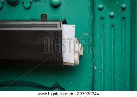 Mailbox with newspaper and mail at a door