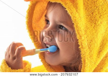 Little Baby Smiling Under A Yellow Towel And Brushing His Teeth
