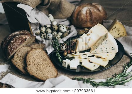 Cheeses lying on black dish and bread situated nearby. Blue cheese, cheese with holes decorated with herbs. Big piece of round bread and tasty slices ready for making sandwiches for a snack.