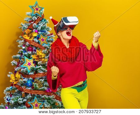 Festive season. smiling young woman in colorful clothes near Christmas tree on yellow background with VR glasses rejoicing