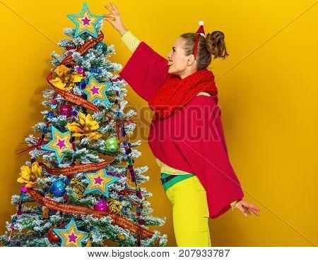 Woman Near Christmas Tree On Yellow Background Decorating