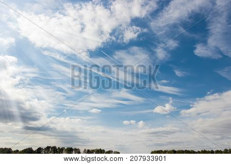 Sky with cumulus and cirrus clouds sun beams and aircraft inversion trail over a trees at summer day