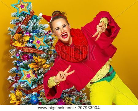 Smiling Woman Near Christmas Tree Showing Victory Gesture