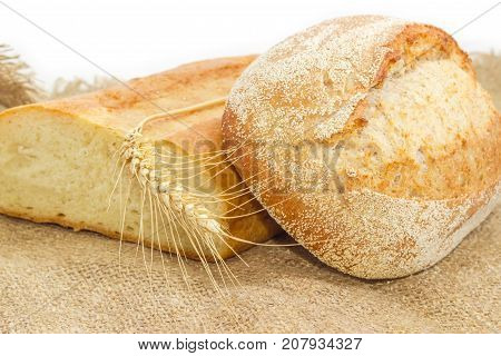 Half of wheat bread and whole loaf of the wheat sourdough hearth bread with bran and ear of ripe wheat on a sackcloth closeup on a white background