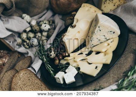 Different kind of cheese - blue cheese, cheese with holes, cheese slices and cubes on black plate. Slices and whole bread on beige background. Herbs and berries as decoration