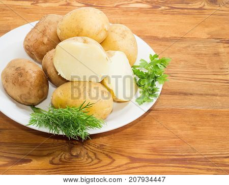 Fragment of white dish with potatoes boiled in their skins with twigs of parsley and dill on a surface of old wooden planks closeup