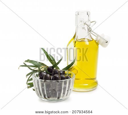 Black olives in small glass bowl glass bottle of the olive oil with open lid and olive branch beside on a white background
