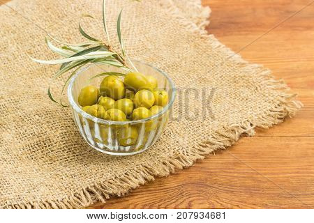 Canned green olives in small glass bowl and olive branch on a sackcloth on a surface of an old wooden planks closeup