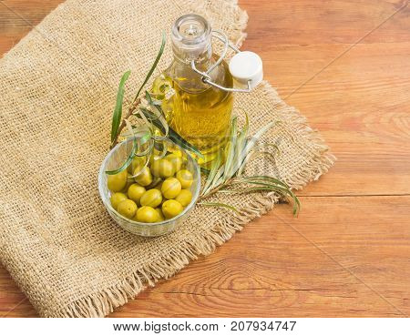 Glass bottle of the olive oil with open lid green olives in small glass bowl and olive branches on a sackcloth on an old wooden planks