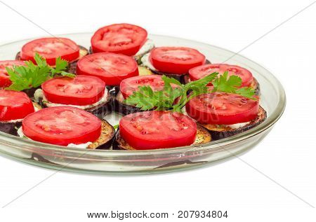 Fragment of the glass dish with chopped by circles roasted eggplants with garlic sauce and covered by chopped fresh tomatoes on a white background