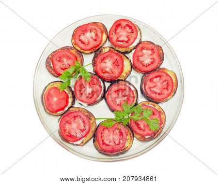 Top view of a glass dish with chopped by circles roasted eggplants with garlic sauce and covered by chopped fresh tomatoes on a white background
