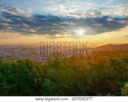 View of the outskirts of the city from hill during sunrise