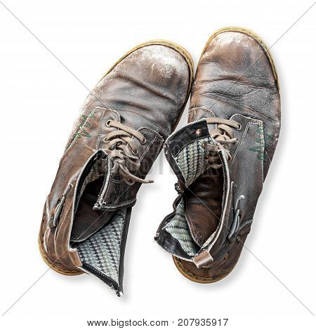 Pair of old used worn out boots isolated on white background. High angle overhead view