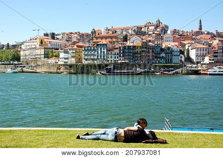young boy resting on the banks of the douro river in portugal