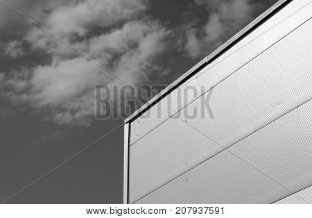 Metal Sided Warehouse Against Sky In Black And White