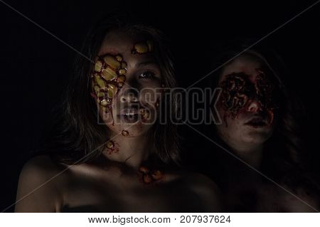 Girls with a realistic Halloween makeup. Girls with sores and blood on their face.