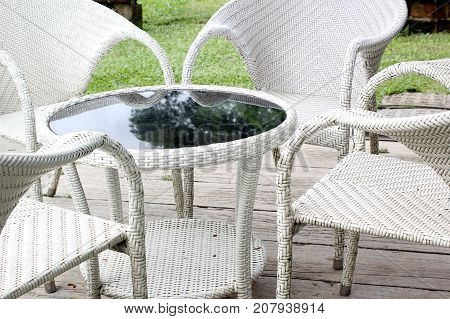 woven wood table and armchair in garden