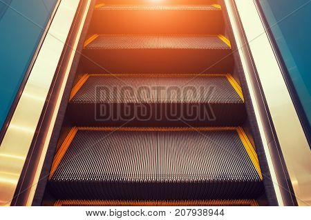 Escalator and step inside building with lighting.