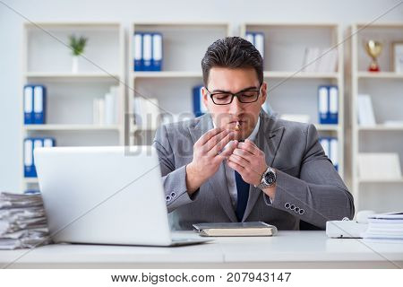 Businessman smoking in office at work