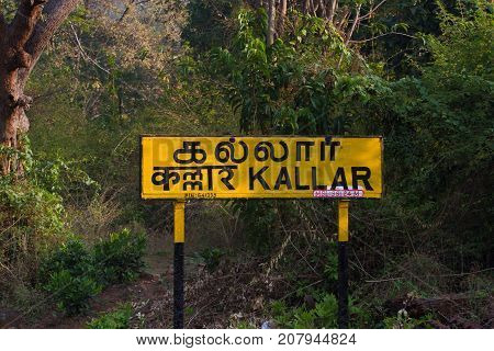 Nilgiri. Railroad sign Kallar written in Tamil nadu official language of Tamilnadu , Hindi and English on a platform of the railway station