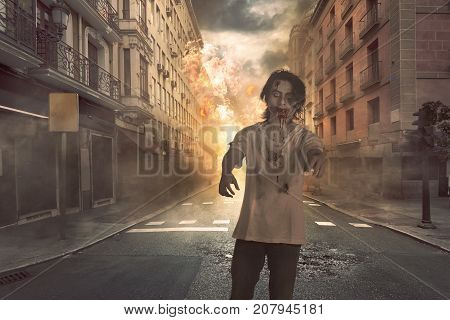 Creepy asian zombie man with blood in his face walking against destruction city