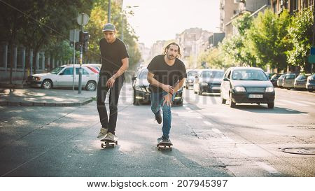 Two Pro Skateboard Rider Ride Skate Through Cars On Street