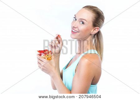 Beautiful Young Woman Eating Cereals And Fruits Over White Background.