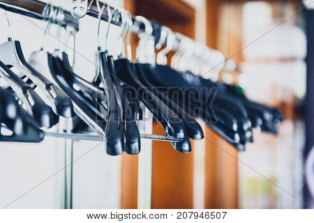 Empty wardrobe stand with black hangers at business event venue. Empty clothing rack at the theatre or business party.