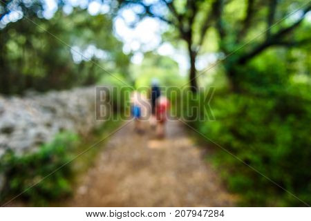 Family Hiking On Country Road With Rock Fence And Woods.