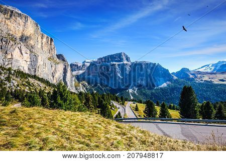 The concept of extreme and ecological tourism. Impressive ridge of dolomite rocks. Picturesque road through the Sella Pass, Dolomites. Indian summer in the Tirol