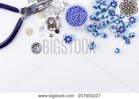 Jewelry making and beading. Seedbeads metal components polyclay purple blue flower beads mix pliers on white background. Selective focus. Top view.