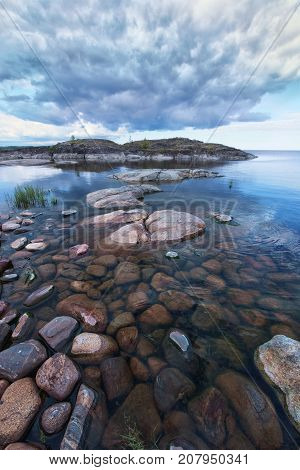 Lakeside photo taken at early morning at Ladoga skerries Karelia region Russia. Severe cloudy sky of this northen landscape is accompanied by harsh rocky lakeside and clean water.