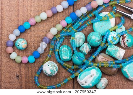 Turquoise beads colorful glass beads seedbeads gemstones mix closeup on wooden background. Selective focus.