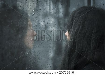 Woman in front of rainy window - Profile image of a young brunette woman with closed eyes thinking in front of rainy window