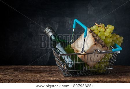 Woman Carrying Basket Household Shopping for lonely evening. Shopping Basket with cheese, grape and wine