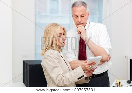Business colleagues using a tablet in their office