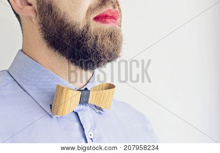 Adult bearded Man Office Manager in a Blue Shirt with Bow Tie and with Red Lipstick on Lips. Happy Boss's Boss Chef day Tolerance concept