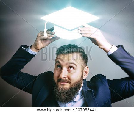 The image of a man in a suit that puts a graduation hat cap on his head. The concept of education online education achieving the goal success and etc.