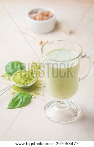 Green tea matcha latte in a glass cup on light background. Concept of a healthy diet, superfood, antioxidant, cleansing