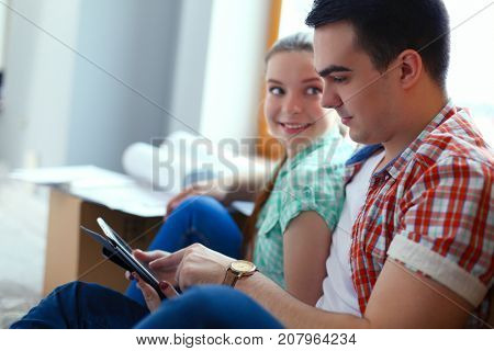 Couple moving in house sitting on the floor with ipad. Couple