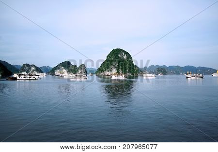View of green islands in Halong Bay at day from a distance with white boats on the water UNESCO World Heritage Site Vietnam Southeast Asia.