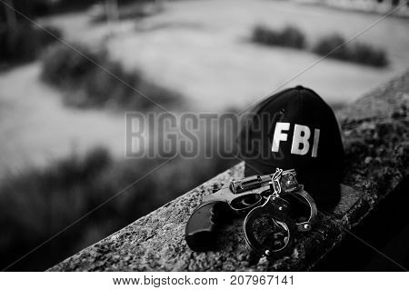 FBI cap with revolver and handcuff outdoor