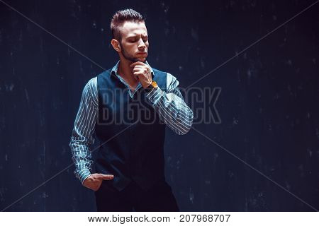 Portrait of sexy macho over dark background wearing a chronograph wrist watch. Masculine man in stylish clothes standing and thinking, hand on chin, looking down.